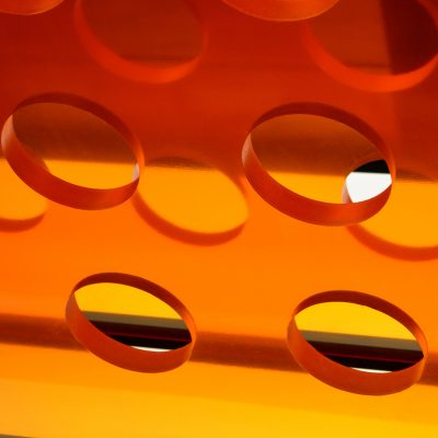 Clear orange plastic abstract with round hole cut outs.